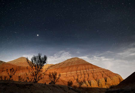 Red mountains in the canyon desert at night starry sky