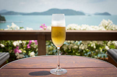 A glass of beer with sea background photo