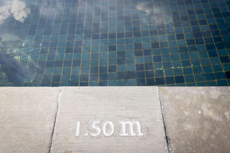 Pool depth sign at the edge of the swimming pool photo