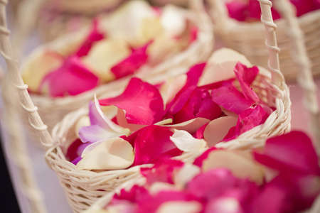 Red and white rose petals in baskets