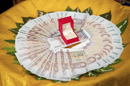 Wedding ring in a red box and Thai money for the bride photo