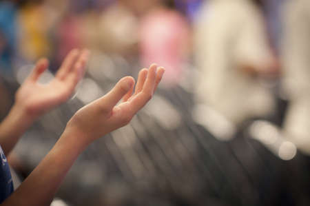 Hands raised like praying or worshiping Stock Photo