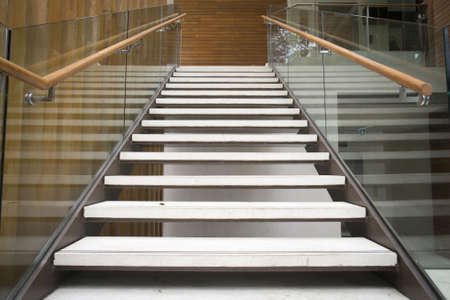 Modern white stairs with wooden handrail Stock Photo