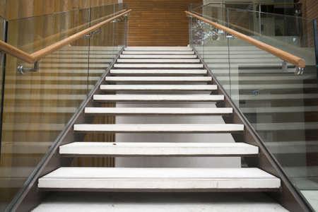 Modern white stairs with wooden handrail Standard-Bild
