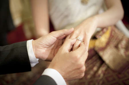 Thai groom putting a wedding ring