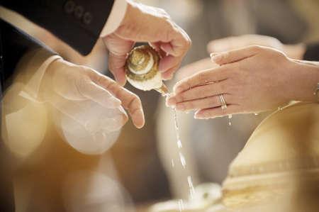 Thai Hochzeit Hand einer Braut empfängt Weihwasser aus Ältesten mit Ehering an ihrem Finger Lizenzfreie Bilder