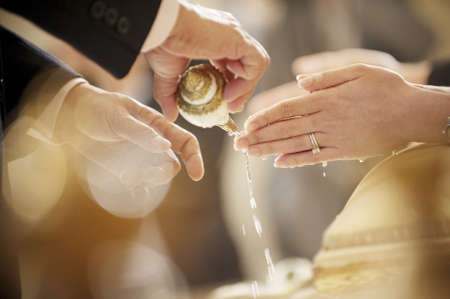 Thai wedding hand of a bride receiving holy water from elders with wedding ring on her finger photo