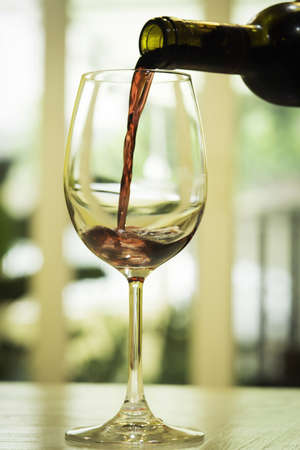 bouteille de vin: Vin rouge étant versé dans un verre à vin