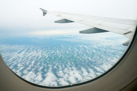 airplane window: Clouds and sky as seen through window of an aircraft