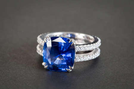 Ring of the jeweler with dark blue sapphire on the black background photo