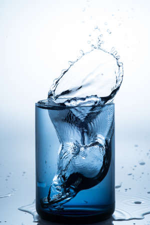 coins drop water into blue glass with white background photo