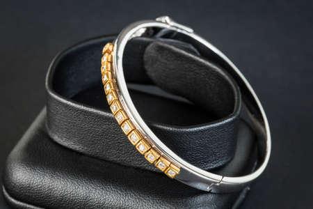 Diamonds and gold bracelet in black background photo