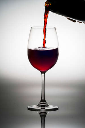Red wine being served into a glass cup on a white background with reflections