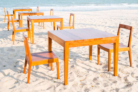 Wooden dining tables on the beach photo