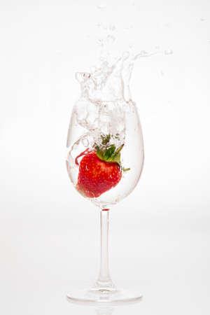 splashing strawberry into water glass on white background photo