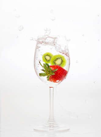 splashing strawberry and kiwi into water glass on white background photo