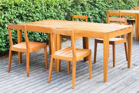 Wooden dining tables in lush garden photo