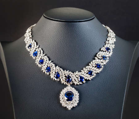 closeup: diamonds with dark blue sapphire necklace on the black background