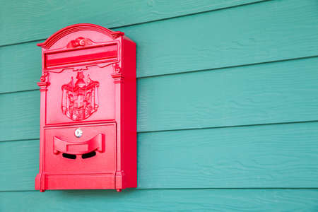 public address: Red mailbox on classic green woonden background