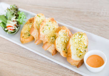 crunchy: Garlic and herb bread on wooden table Stock Photo