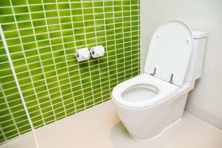 a toilet seat: Clean, white toilet and paper rolls with Lime green mosaic tiles wall