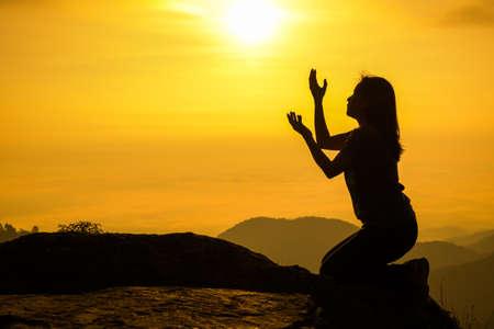 mujer rodillas: Silueta de la mujer que se arrodilla y que ruega sobre el fondo hermoso amanecer