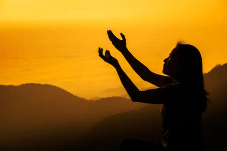 Silhouette of woman kneeling and praying over beautiful sunrise background