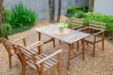 patio chair: Wooden dining tables in lush garden