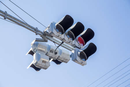 Red color on the traffic light with a beautiful blue sky in background Imagens