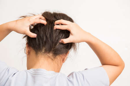 Woman suffering from an headache itching her head