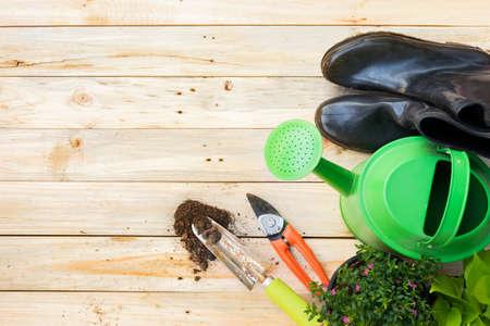 ガーデニング ツール、水まき缶、種子、植物、ビンテージの木製テーブルの上の土壌。フリー テキスト スペースとガーデンのコンセプトの背景に