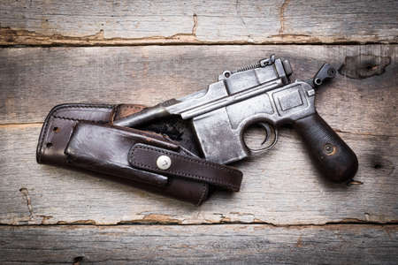 flintlock: vintage submachine gun Mauser on old wooden background