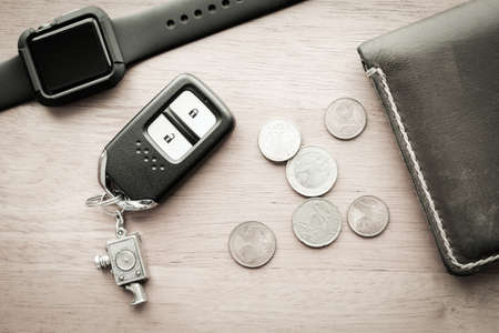 billfold: Watch with wallet and car remote key on wooden table - vintage filter effect Stock Photo