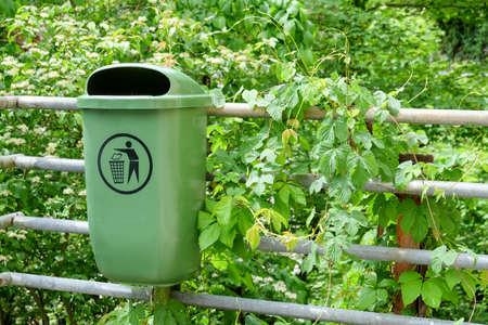 Green plastic dust bin in garden