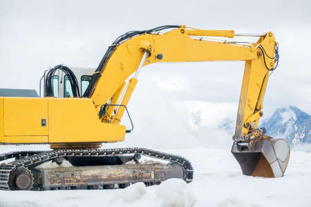 Clearing by the excavator of snow drifts Stock Photo