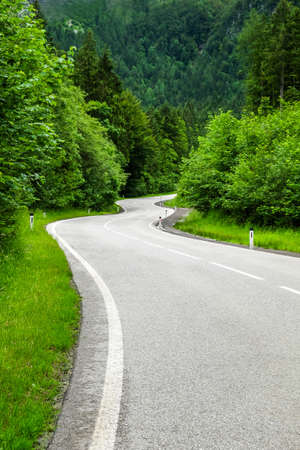 The road curves up the mountain. Line yellow and white road