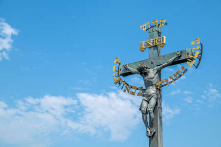 Jesus Christ on cross with blue sky. Jesus christ statue on Charles Bridge in Prague , Czech Republic.