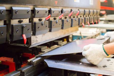 worker in factory at metal skip machine putting work piece in Foto de archivo
