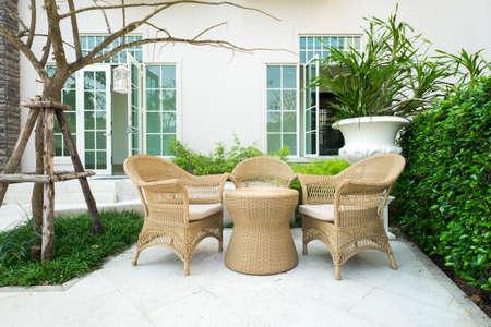 Rotan stoel in de tuin Stockfoto