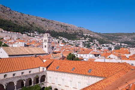 Old Town houses with red tiled roofs and rocky green idyllic island in background, Dubrovnik, Dalmatia, Croatia