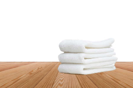 Stacked white spa towels on wooden background Stock Photo