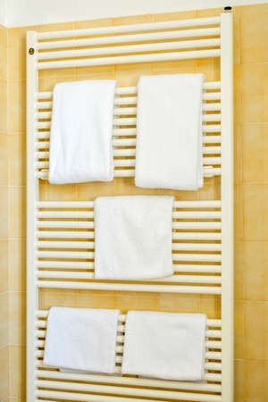 Clean white towel on a hanger prepared to use in bathroom Stock Photo