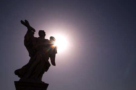 Statua in marmo alla luce del sole dell'angelo con la croce, uno dei dieci angeli sul ponte di San Angelo, simboli della passione di Cristo, Roma, Italia Archivio Fotografico - 96171714