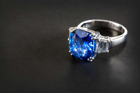 Ring of the jewelry with dark blue sapphire on the black background Stock Photo