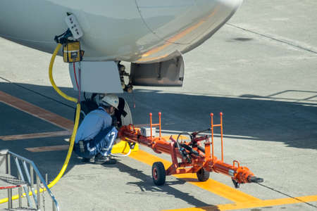 Technicians in signal vests prepare the aircraft for flight