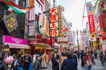 OSAKA, JAPAN - JAN 15 2016: Crowds walk below the signs of Dotonbori area in Osaka, Japan.