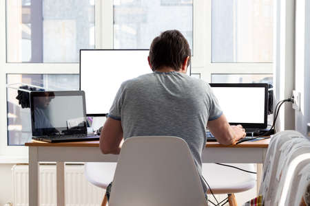 A man in a gray t-shirt is sitting at a workplace with two laptops and a monitor near the window. Remote work from home in quarantine. Back view