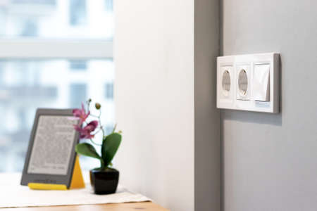 Group of white european electrical outlets and a switch located on a gray wall in a light modern kitchen with flower and e-book on the table by the window. Selective focus