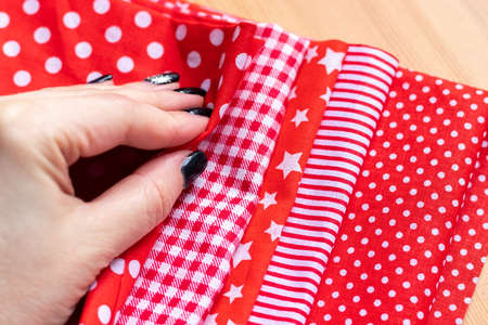 Female hand on a pile of five types of red and white cotton fabrics with different prints: checkered, striped, circle, star, polka dot. Selective focus. Closeup view