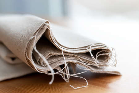 Roll of natural linen fabric with protruding threads on a wooden table. Selective focus. Closeup view. Blurred background